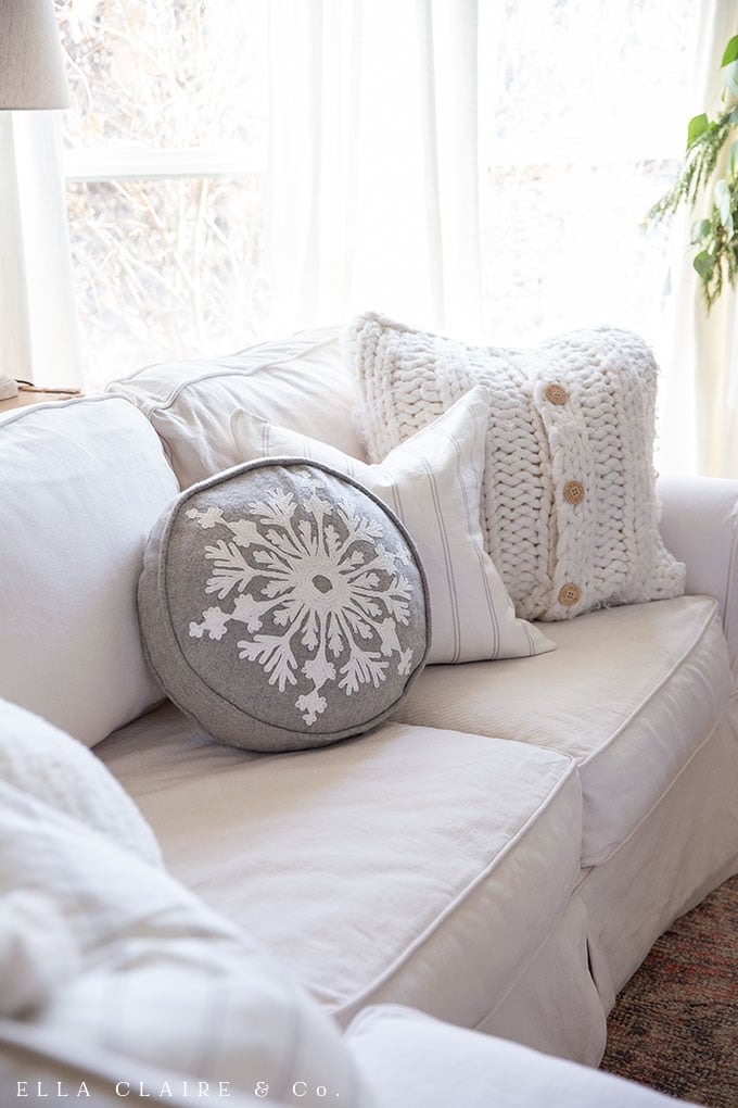 snowflake Christmas pillow ion a cozy sectional in front of the fireplace.