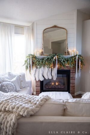 An elegant gold mirror on a mantel draped with fresh and faux garland with cream stockings.