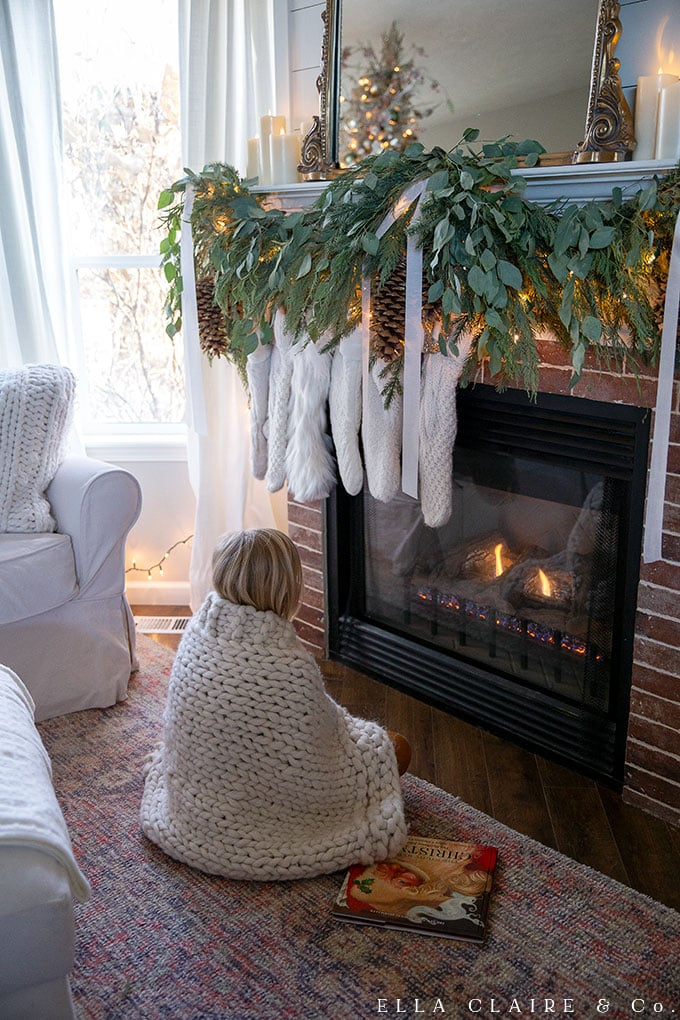 Cozy girl in front of the Christmas mantel and fireplace