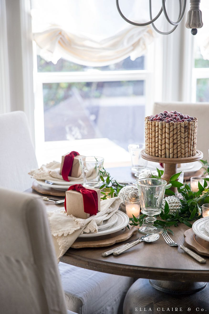 A sweet holiday tablescape with a pirouette/ pirouline wafer cookie cake and Christmas gifts wrapped in Kraft paper and tied with a red velvet bow at each place setting.