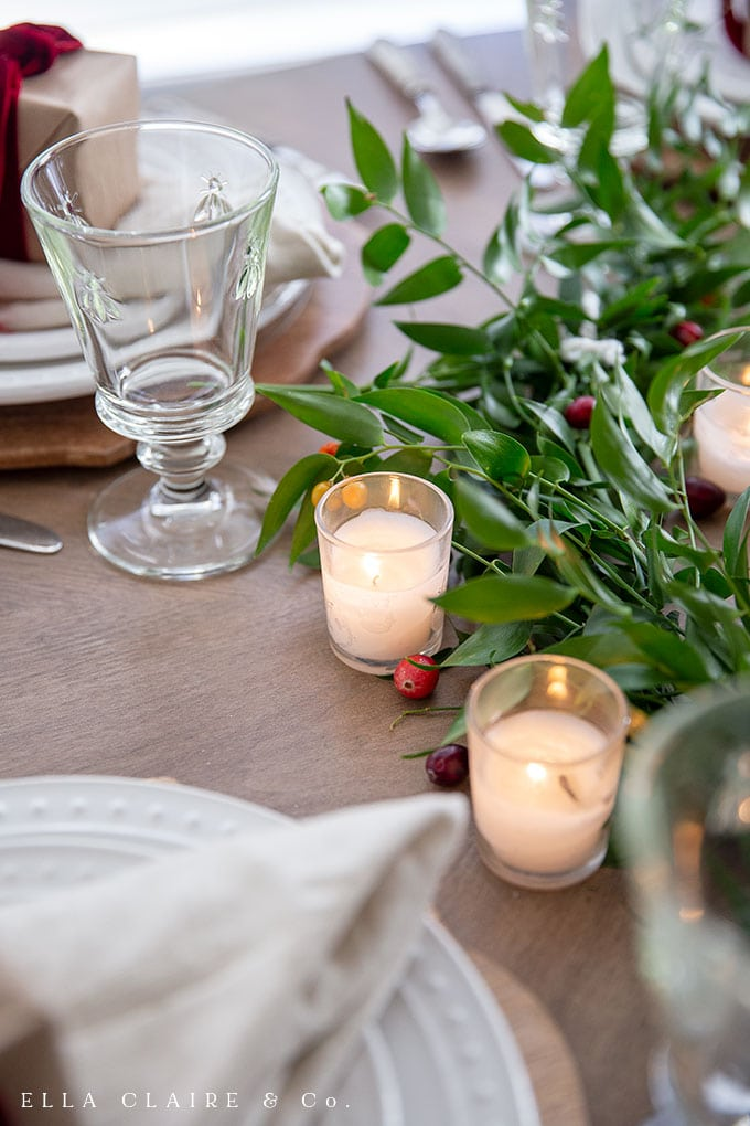 candlelight and greenery with cranberries
