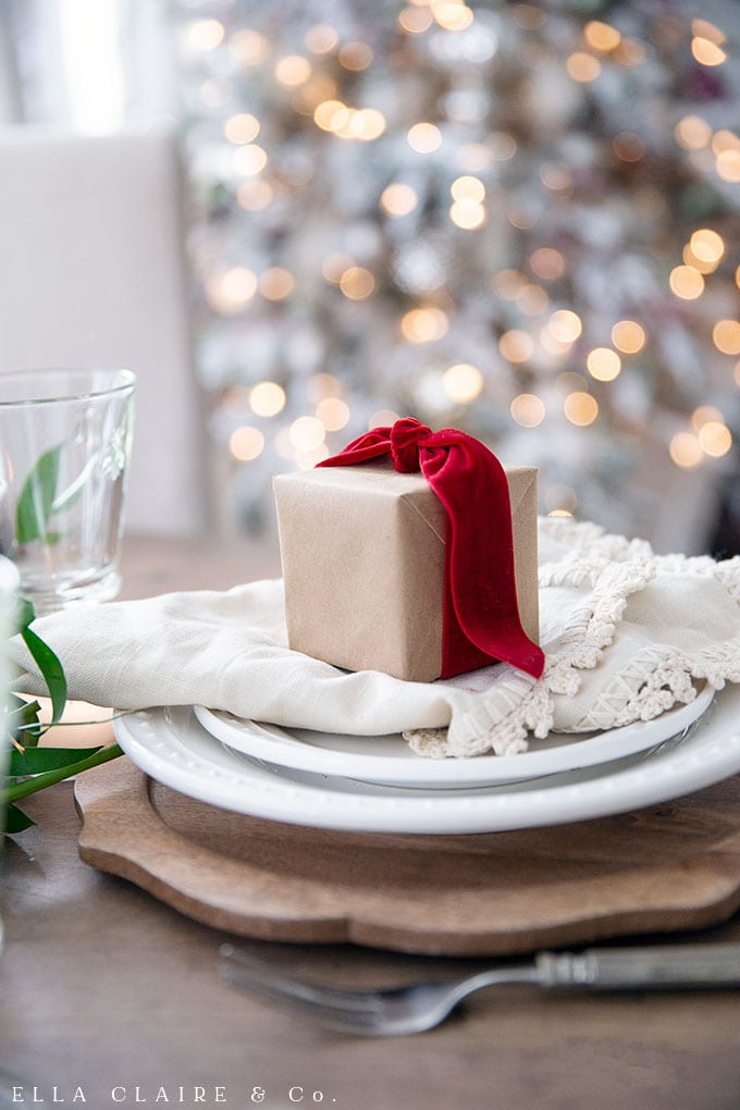 Christmas gifts wrapped in Kraft paper and tied with a red velvet bow at each place setting with the warm glow of candlelight