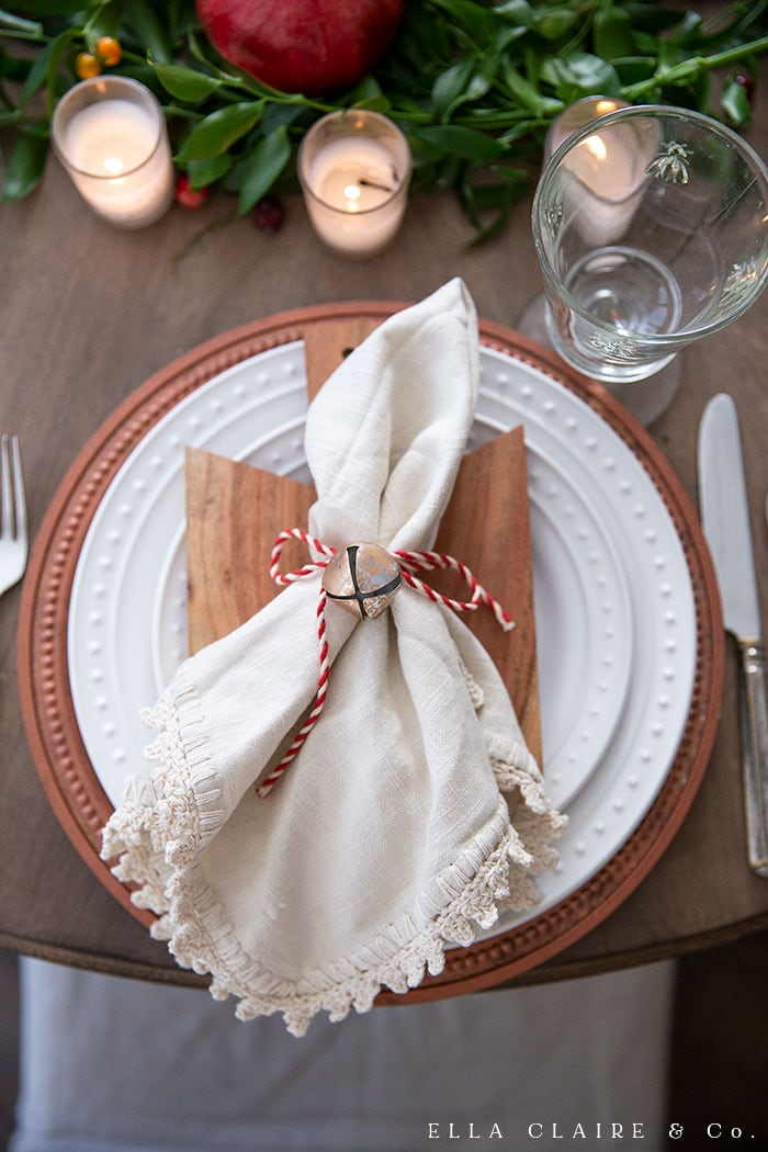 Tie a bell onto a napkin for an easy napkin ring and create this DIY Christmas matching vintage bell and candle centerpiece.
