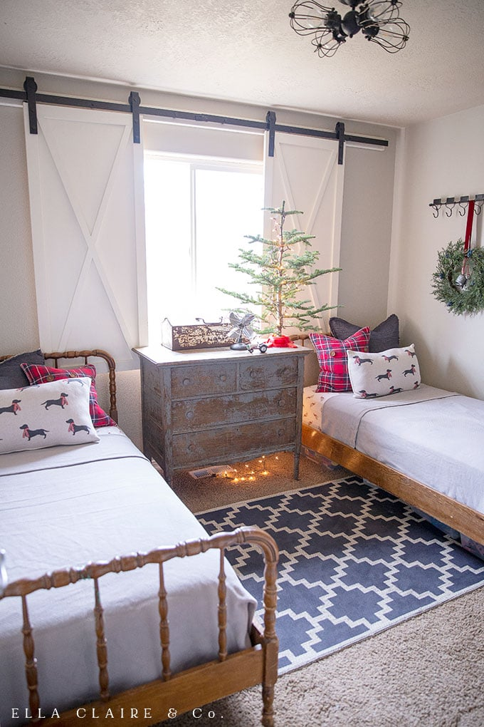 Adding Christmas cheer to children's bedrooms is easy and magical with simple Christmas decor swaps. This Farmhouse Christmas little boys' bedroom features red and navy blue with plaid and dogs with scarves accents.