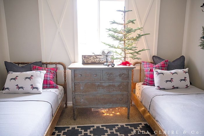 red plaid navy blue Christmas bedroom with farmhouse accents including flannel sheets with dogs in scarves and also plaid pillows.