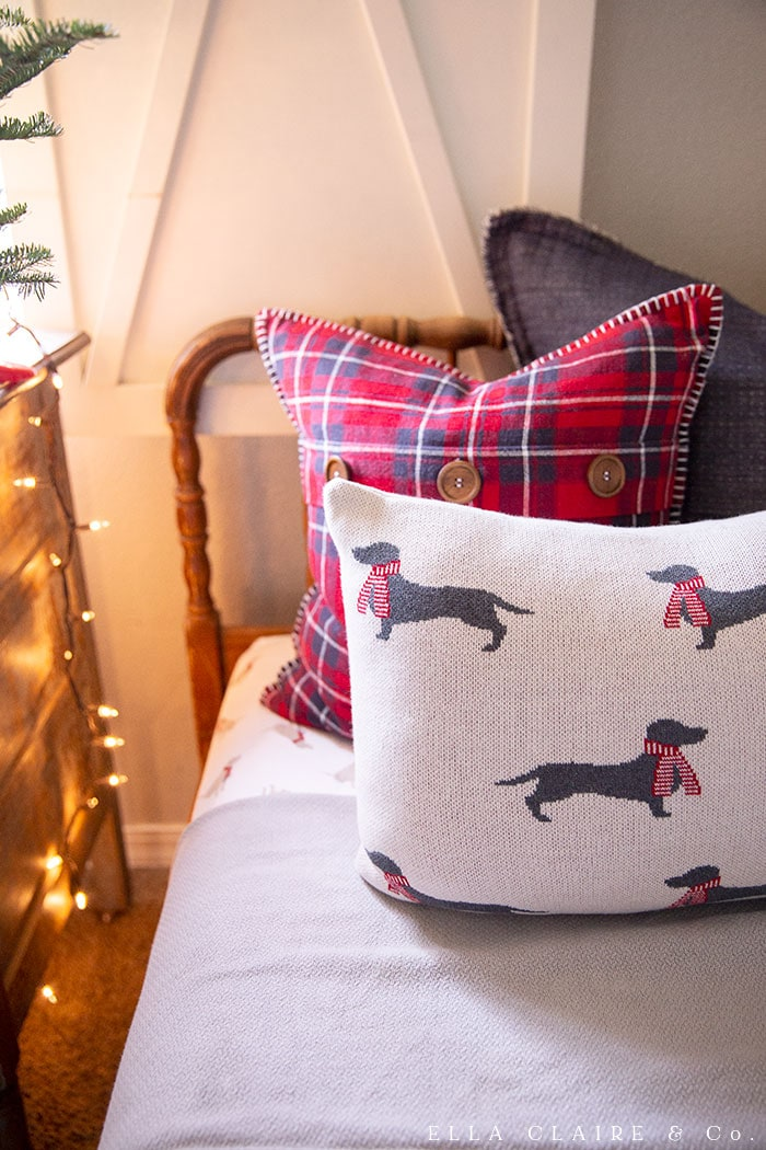 Dog in scarves, red plaid and navy pillows are a festive addition to a little boys farmhouse Christmas bedroom.