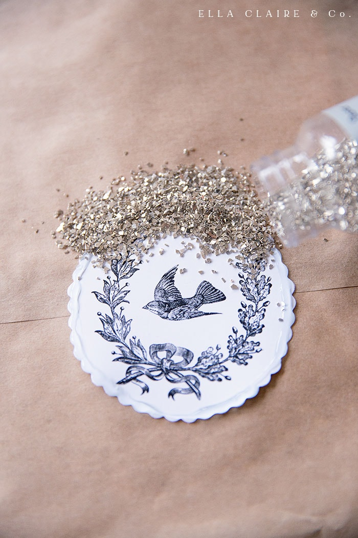 pouring glass glitter on free printable vintage bird wreath ornaments for a vintage inspired Christmas tree
