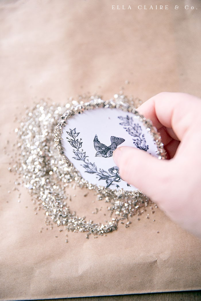 adding glass glitter to free printable vintage bird wreath ornaments for a vintage inspired Christmas tree