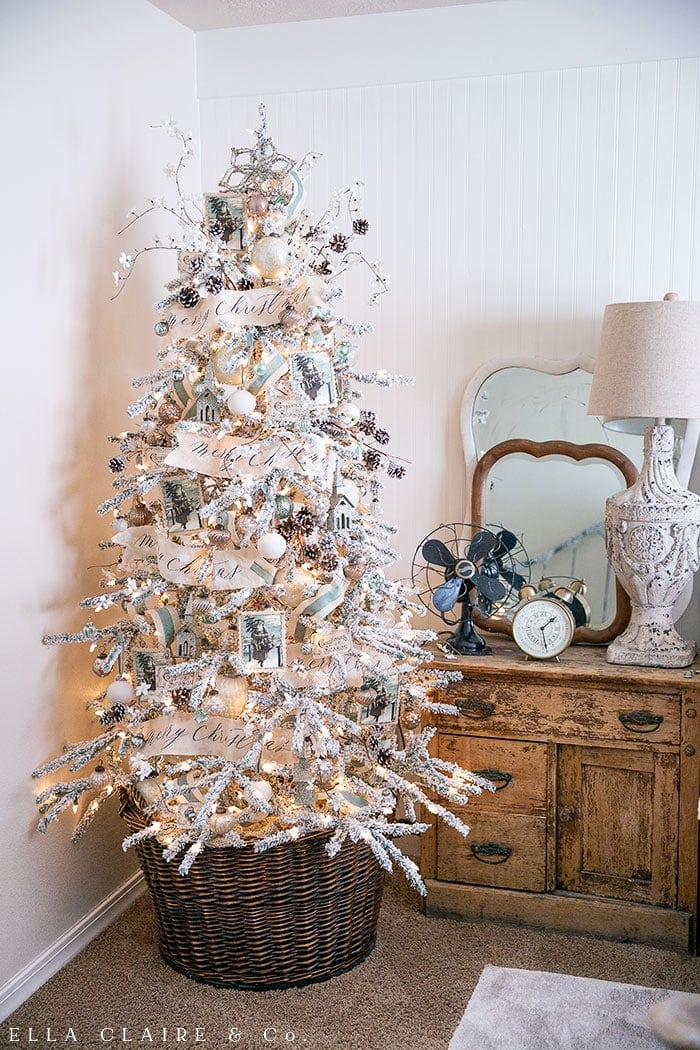 Beautiful vintage farmhouse flocked Christmas tree with blue and teal accents, vintage Santa ornaments, mercury glass, tea dyed Merry Christmas banners, and other sweet antique touches.