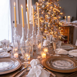 An enchanting New Year's Eve tablescape with vintage clock face printables under clear glass plates at each place setting, accented by candlelight and antique gold and silver pieces.