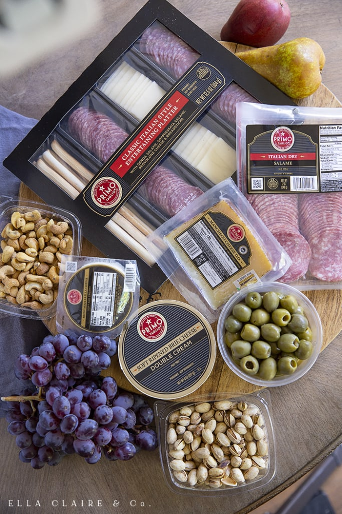 Different ingredients for a simple but delicious charcuterie tray including meats, cheeses, fruits, breads, crackers, olives, and nuts.