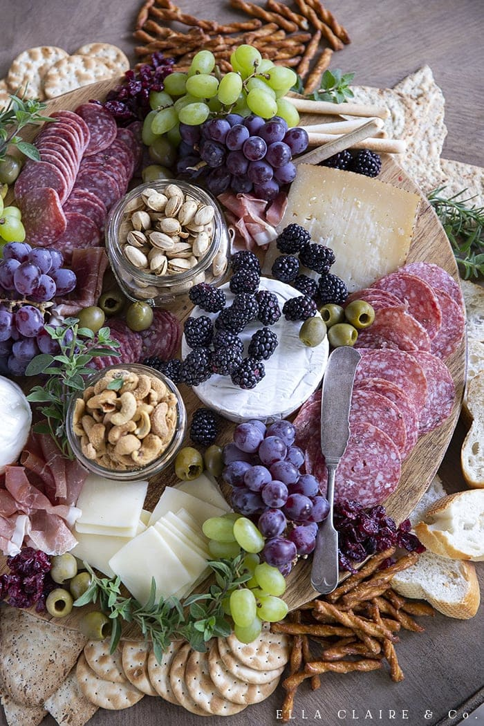 A beautiful charcuterie tray with meats, cheeses, fruits, breads, crackers, olives, and nuts.