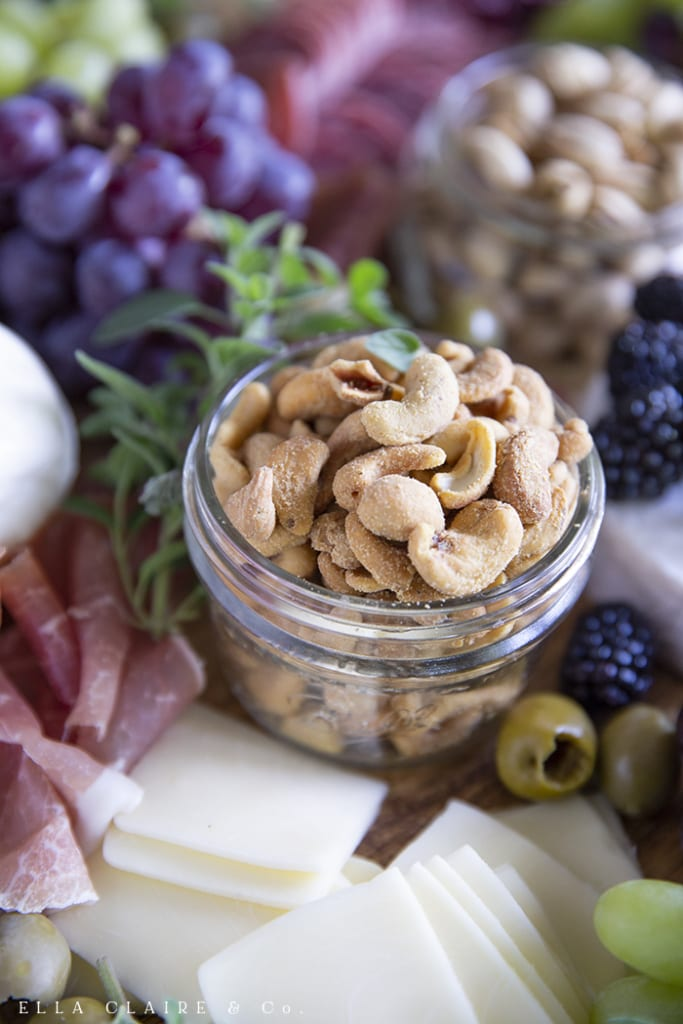 Nuts in a bowl as part of a beautiful charcuterie board.