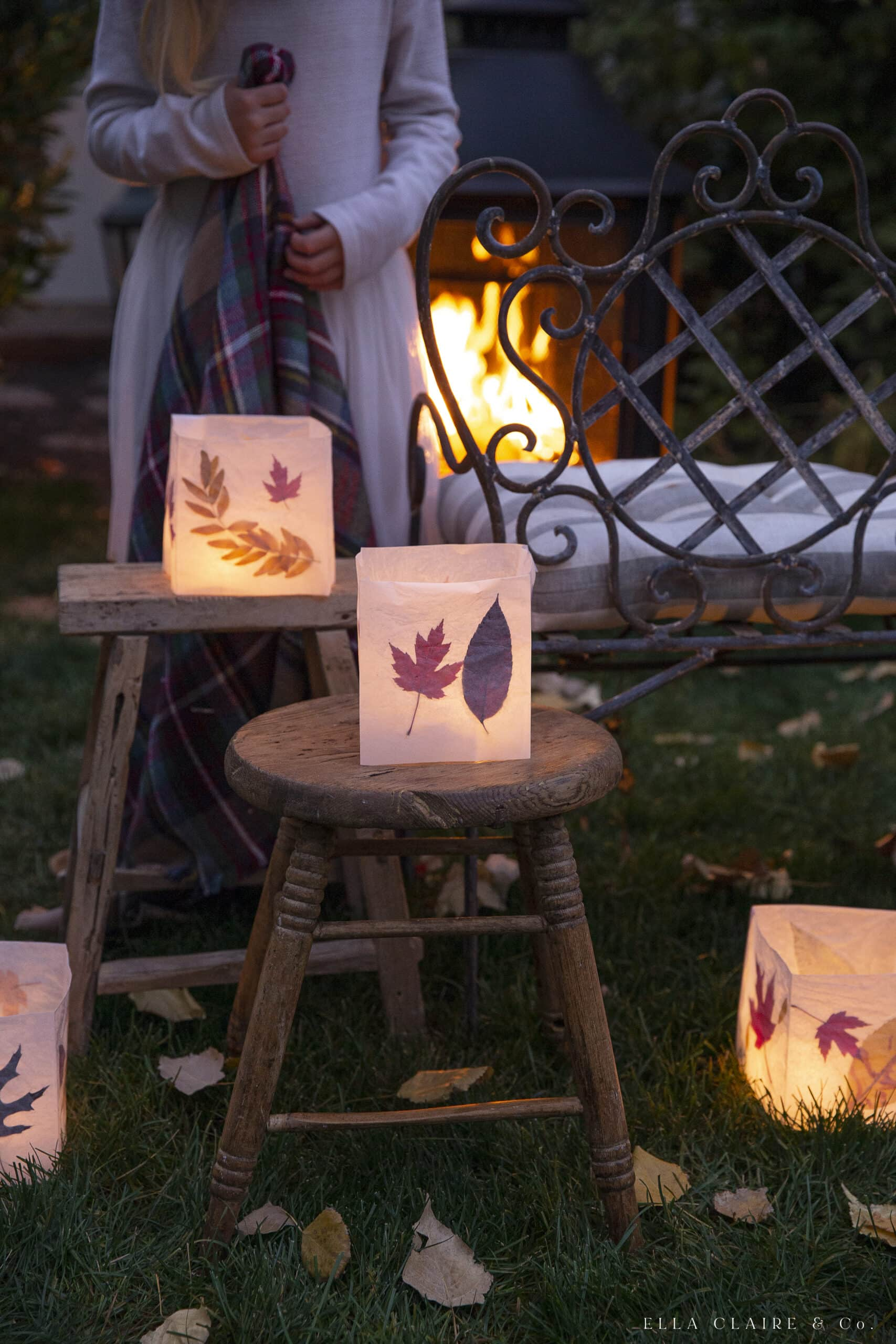 Fall leaves luminaries stacked on stools for outdoor fall decorations