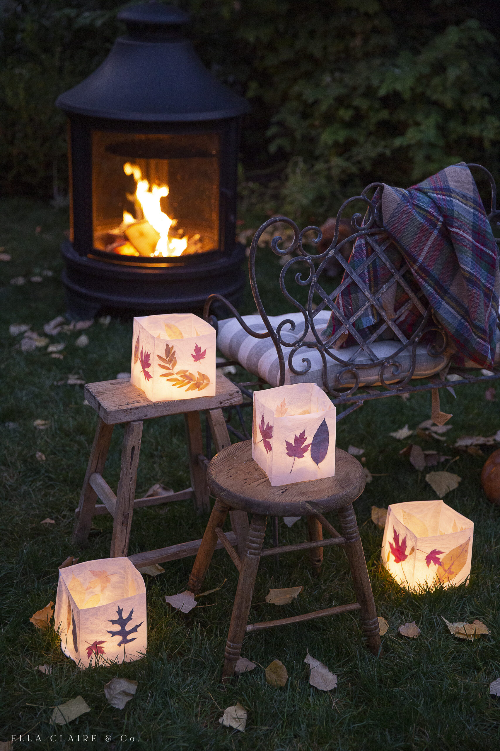 DIY luminaries stacked on stools and ground for outdoor fall decorations