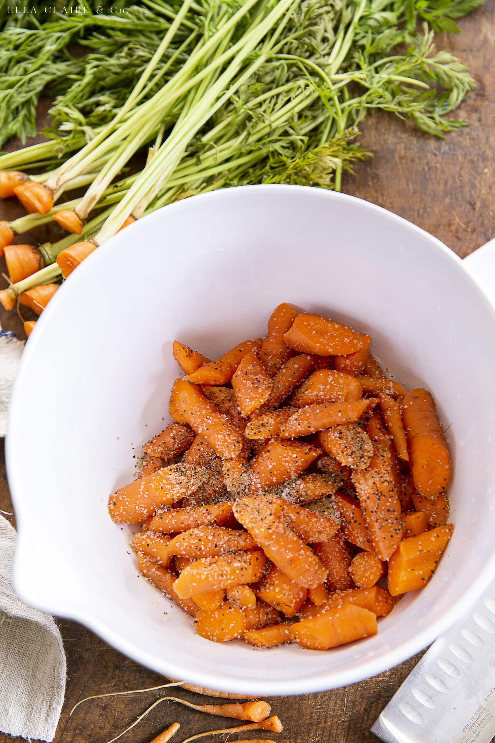 Mixing carrots with salt pepper and oil