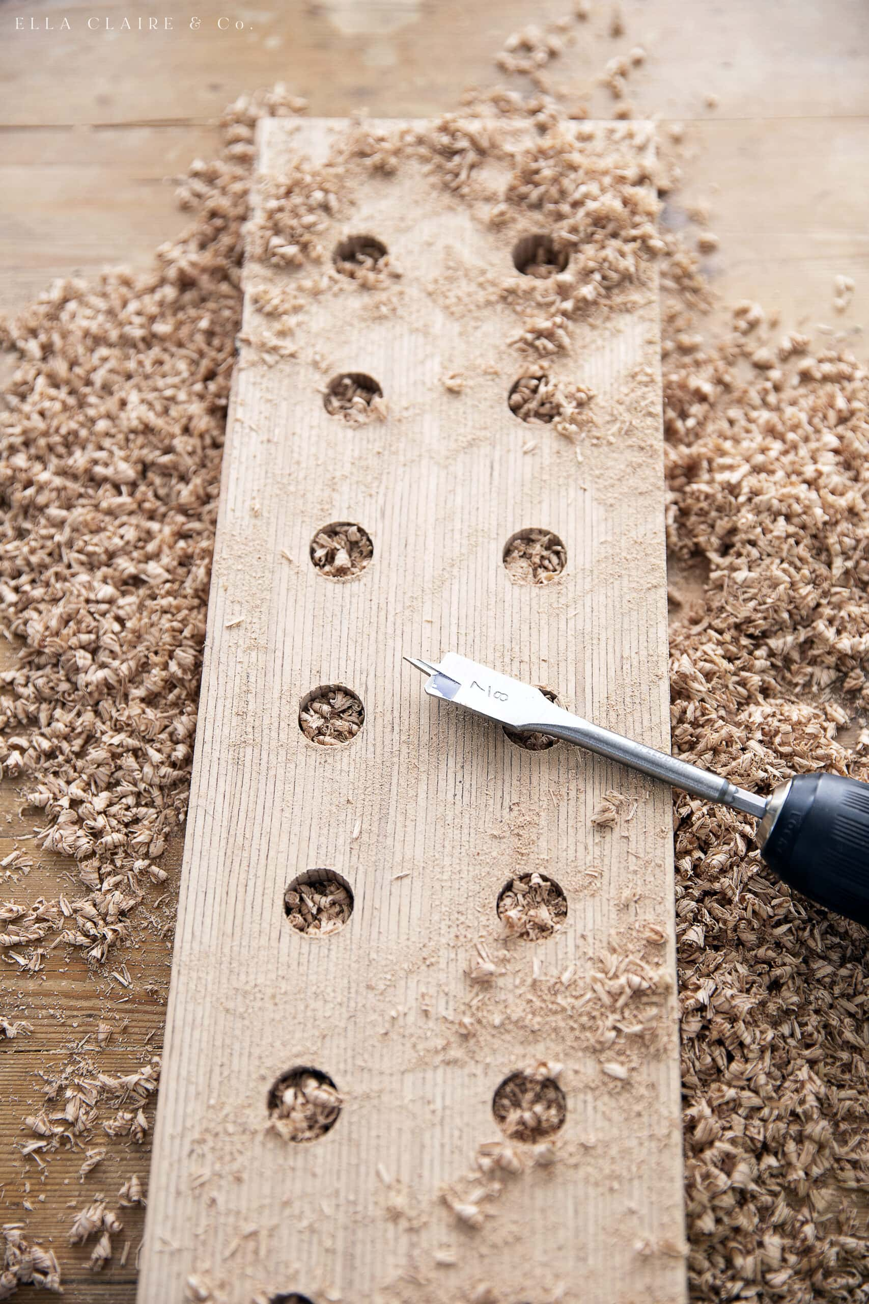 finish drilling all holes in wooden candle holders with paddle bit