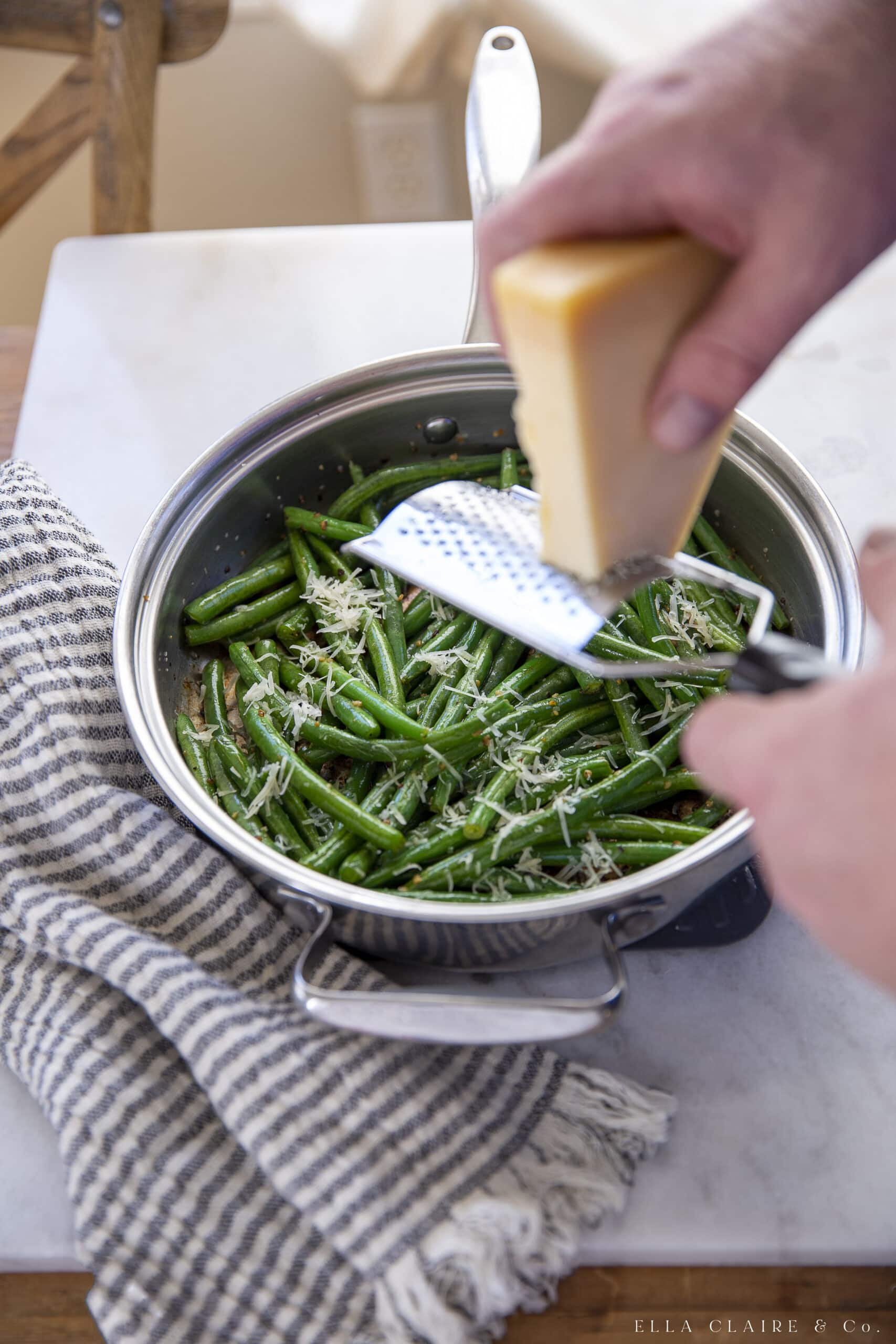 Freshly grating parmesan cheese over sautéed green beans.