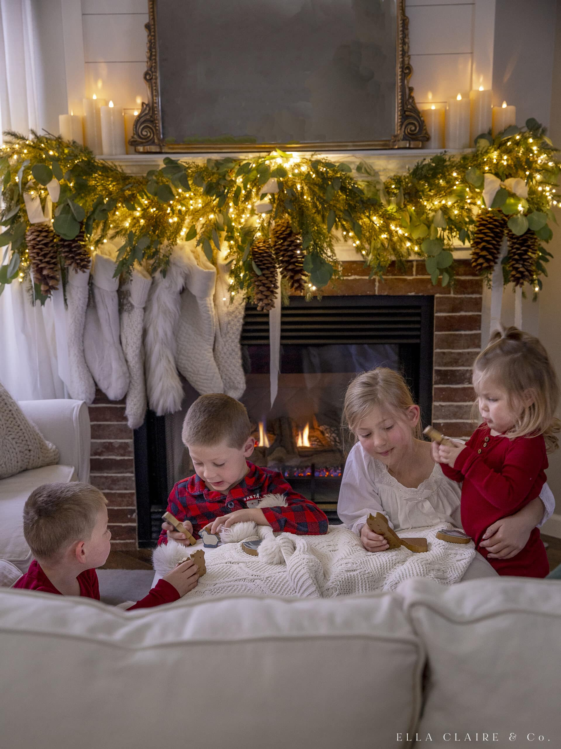 kids with wooden nativity in front of fireplace