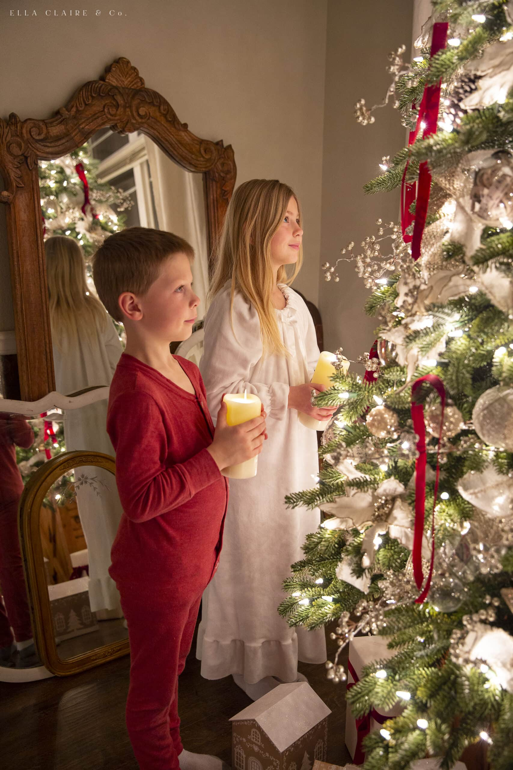 children holding candles and looking at Christmas tree
