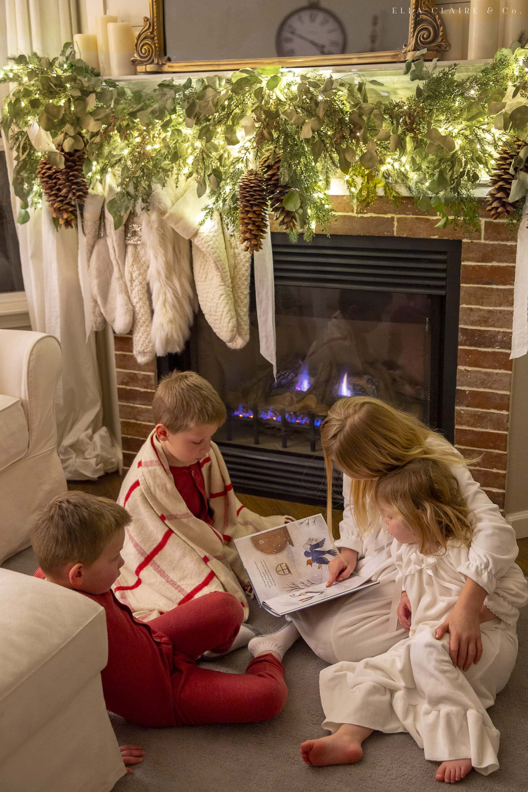 children reading Christmas stories by the fireplace