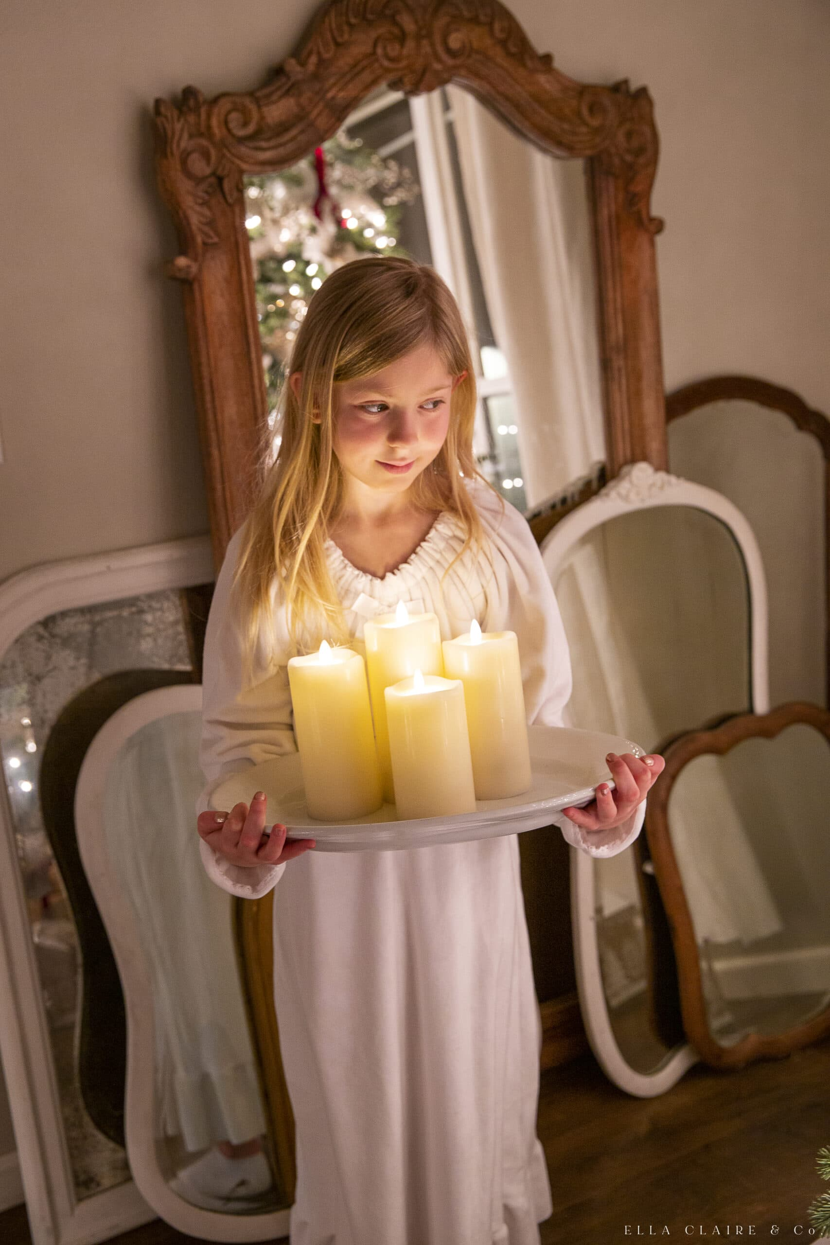 little girl holding Christmas candles in nightgown