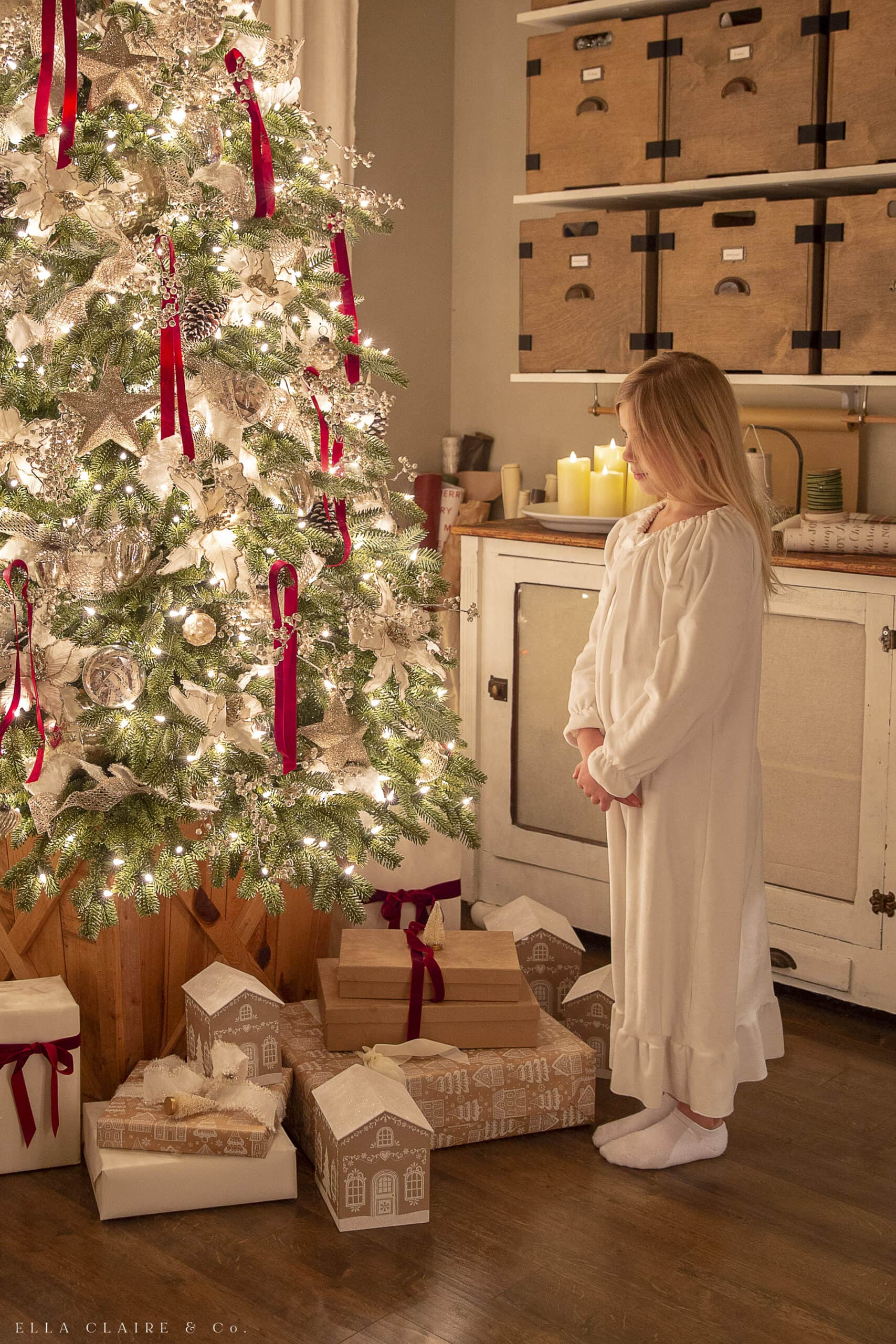 little girl in nightgown. looking at Christmas tree lights at night