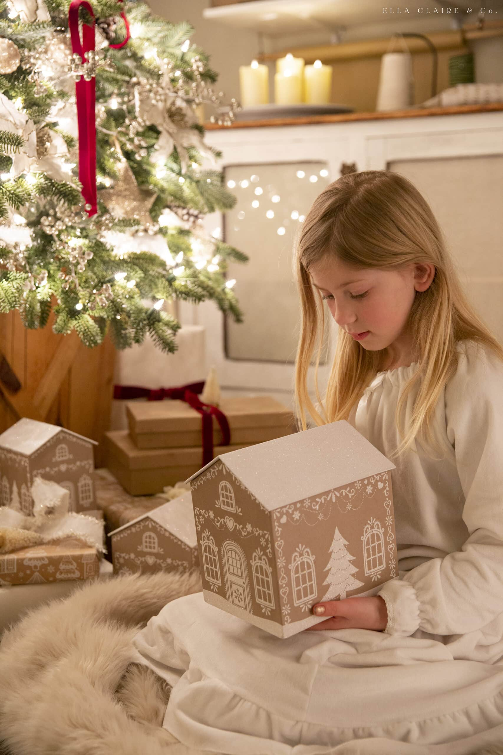gingerbread gift box held by little girl in Christmas pajamas