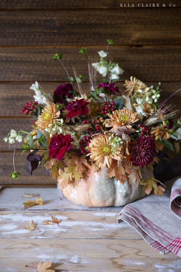rustic warm fall flower centerpiece in a pumpkin