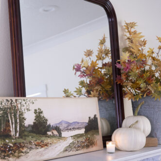 canvas landscape art on mantel decorated for fall